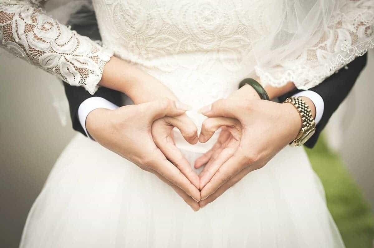 para młoda tworzy serce rękoma w formie podziękowania dla gości weselnych