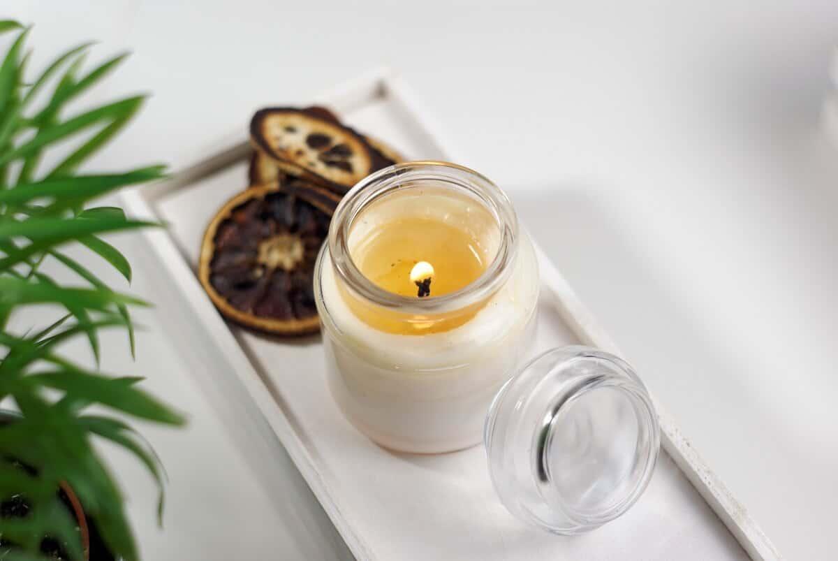 zapalona zapachowa świeca sojowa na białym stole, obok kwiat liściasty