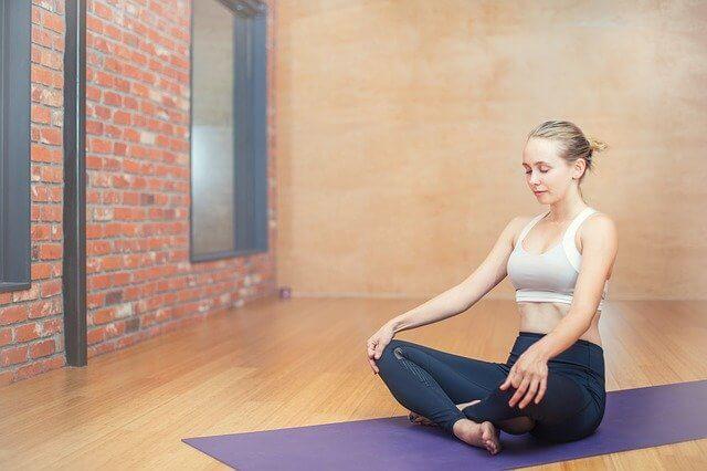 kobieta medytująca na granatowej karimacie w specjalnej sali do medytacji
