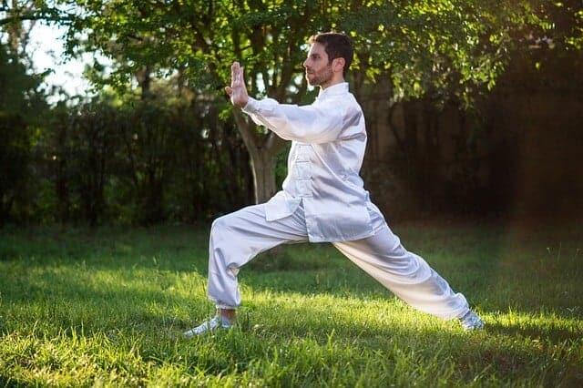 technika relaksacyjne w postaci yogi przedstawiona przez mężczyznę w białym stroju na trawie